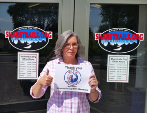 Administrative Director, Mary Jo Foster, holds a big thank you from Sharetrails.Org/BRC to the Mile Hi Jeep Club.