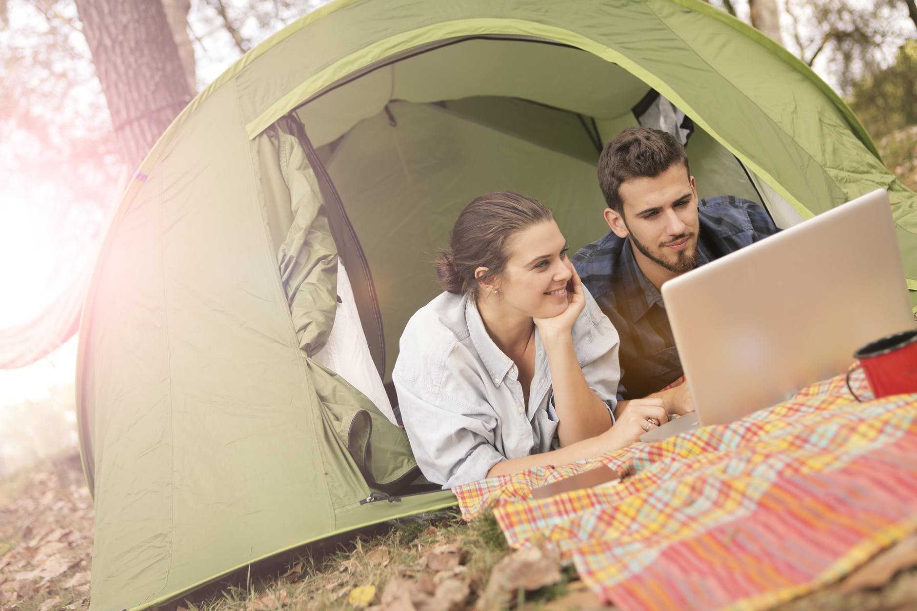 happy couple using laptop in tent